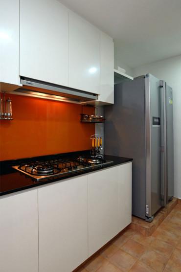 Kitchen renovation. Contemporary kitchen with white glossy kitchen cabinets with bright orange backsplash. LED lights. Quartz kitchen top.